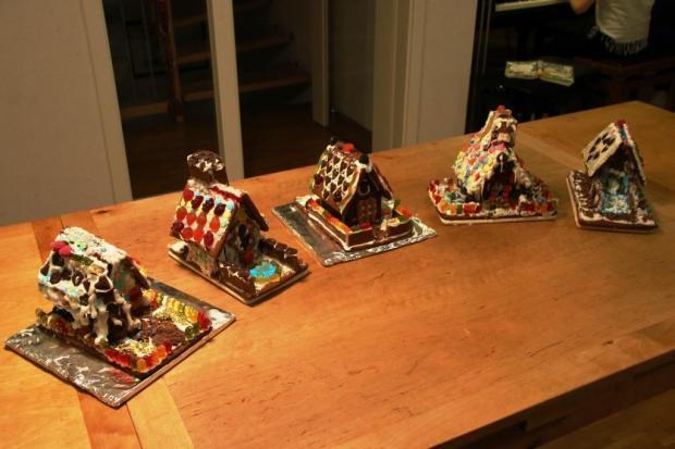 Fünf bunte Lebkuchenhäuser unterschiedlichsten Stils stehen auf einem Tisch aufgereiht.